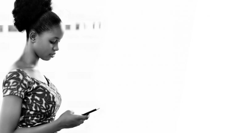 A black & white photo of a woman looking at her phone.
